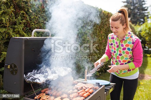 696841580 istock photo Woman grilling food on barbecue 957011390