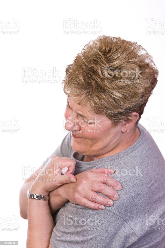 Woman grimacing wearing grey top clutching her shoulder stock photo