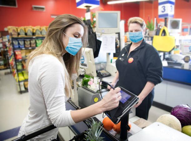 Woman grocery shopping wearing surgical mask due to Covid-19 virus stock photo