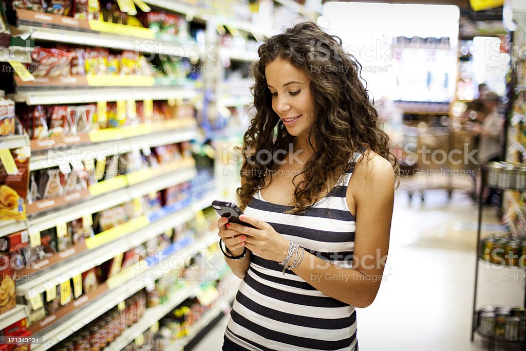 Woman Grocery Shopping with Mobile Phone royalty-free stock photo