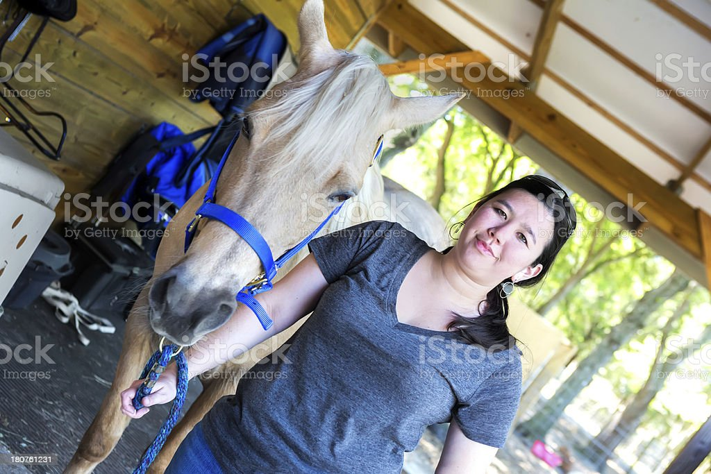 Woman grooming her horse royalty-free stock photo