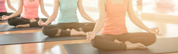 woman group exercising and sitting in yoga lotus position in yoga classes woman group exercising and sitting in yoga lotus position in yoga classes yoga class stock pictures, royalty-free photos & images