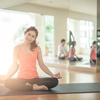 woman group exercising and sitting in yoga lotus position