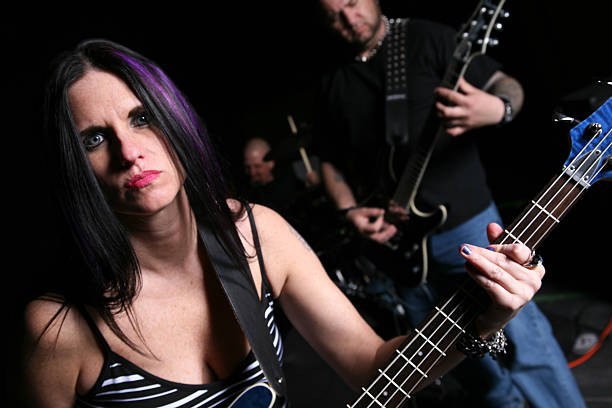 Woman Guitarist In A Punk Band A guitar player in front of the band. goth stock pictures, royalty-free photos & images