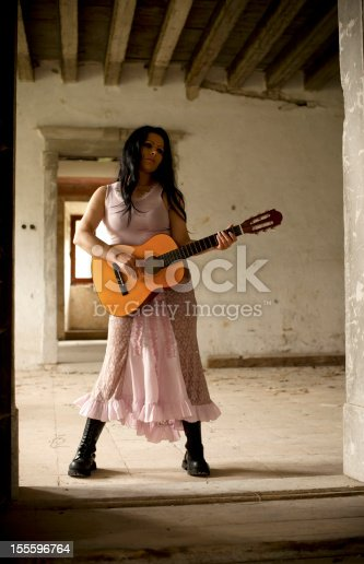 Beautiful young woman playing acoustic guitar inside the abandoned Lože castle (Leitenburg) in Vipavska dolina, Slovenia.