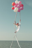 Woman gymnast flies on balls high in the sky and demonstrates twine.