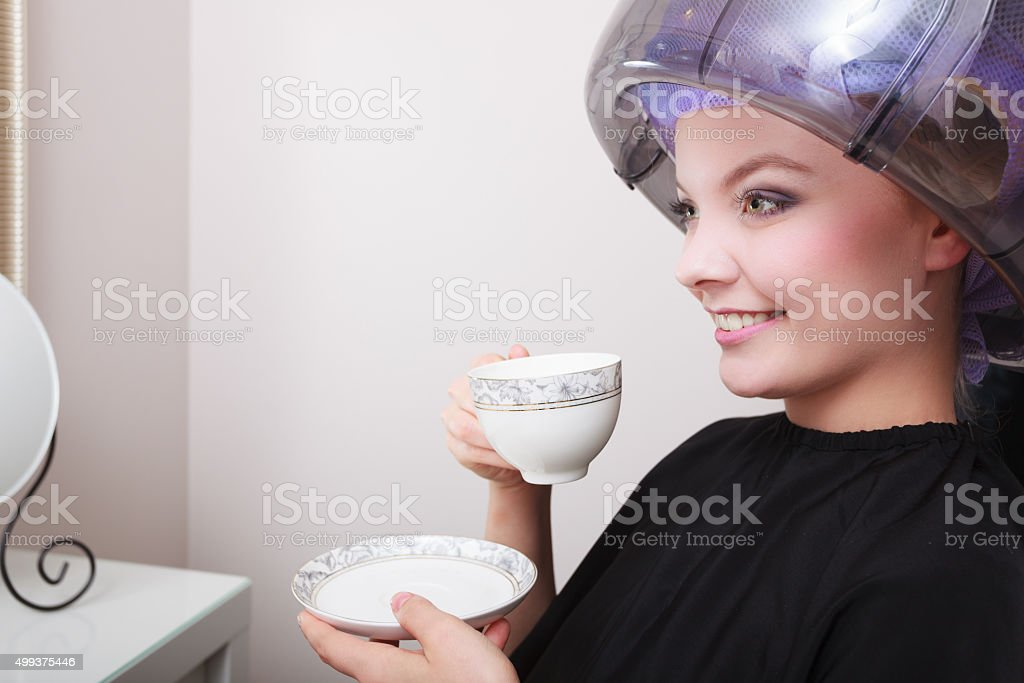 Woman hair rollers curlers drinking coffee tea hairdryer beauty salon stock photo