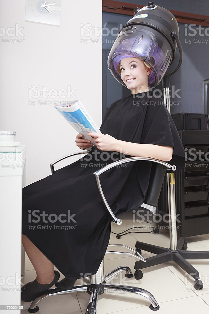 Woman hair rollers curlers reading magazine hairdryer beauty salon royalty-free stock photo