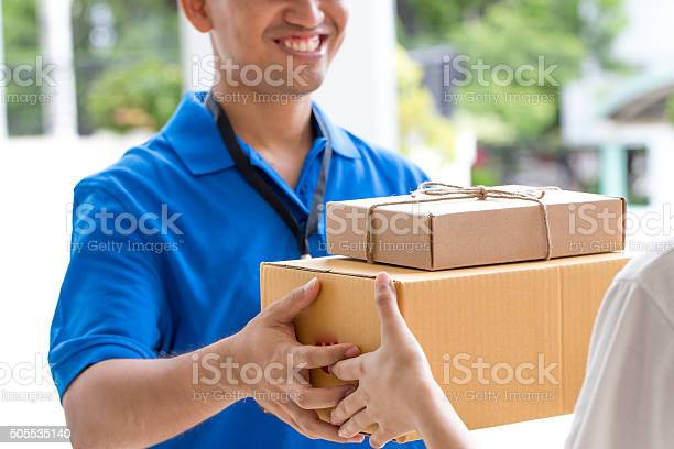 Woman Hand Accepting A Delivery Of Boxes From Deliveryman Stock Photo - Download Image Now