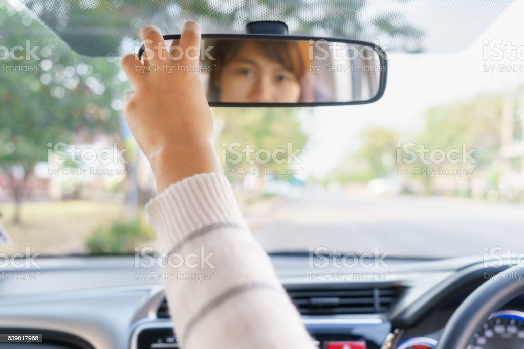 Woman hand adjusting rear view mirror of her car - foto de acervo