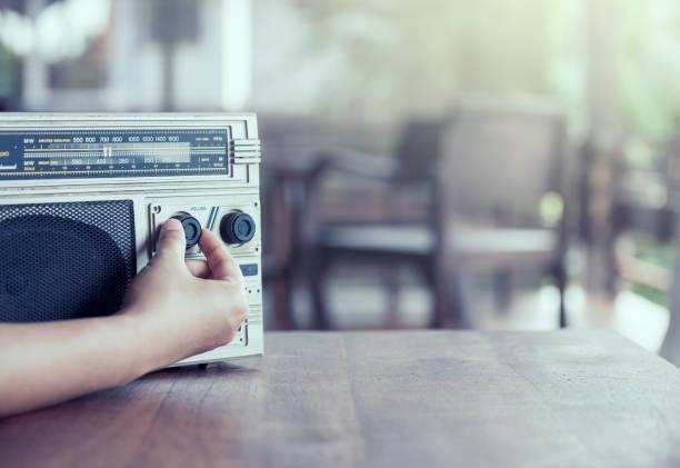woman hand adjusting the sound volume on retro radio cassette stereo - altoparlante hardware audio foto e immagini stock