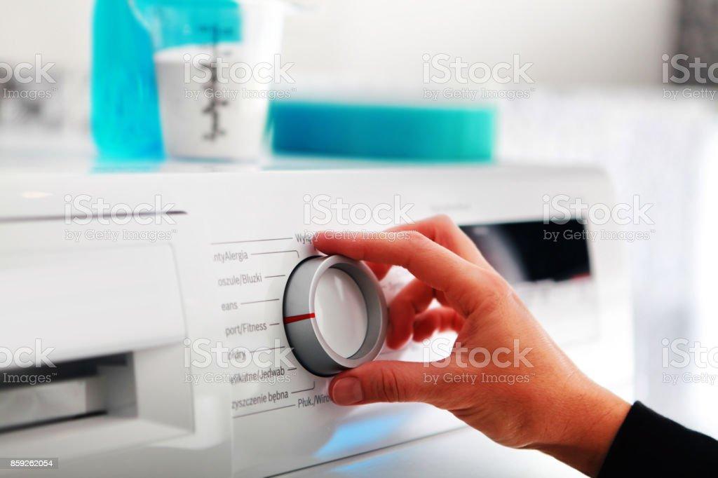 woman hand adjusting washing machine stock photo