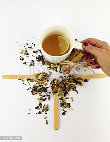 istock woman hand and herbal tea 1047013892