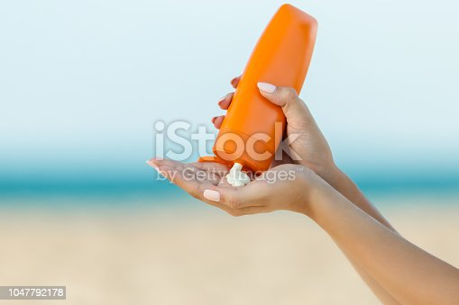 Woman hand apply sunscreen on the beach