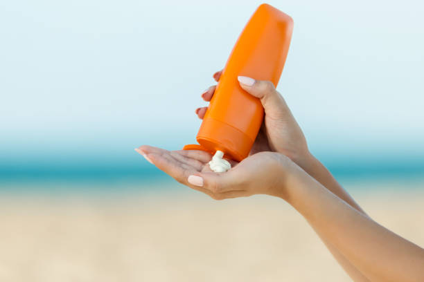 Woman hand apply sunscreen on the beach stock photo
