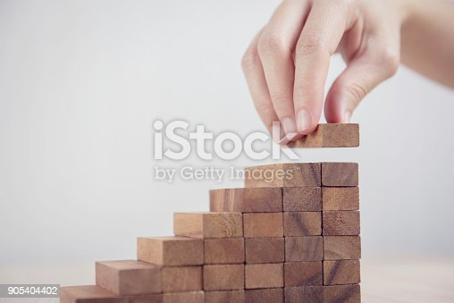 istock Woman hand arranging wood block stacking as step stair. Business concept growth success process. 905404402
