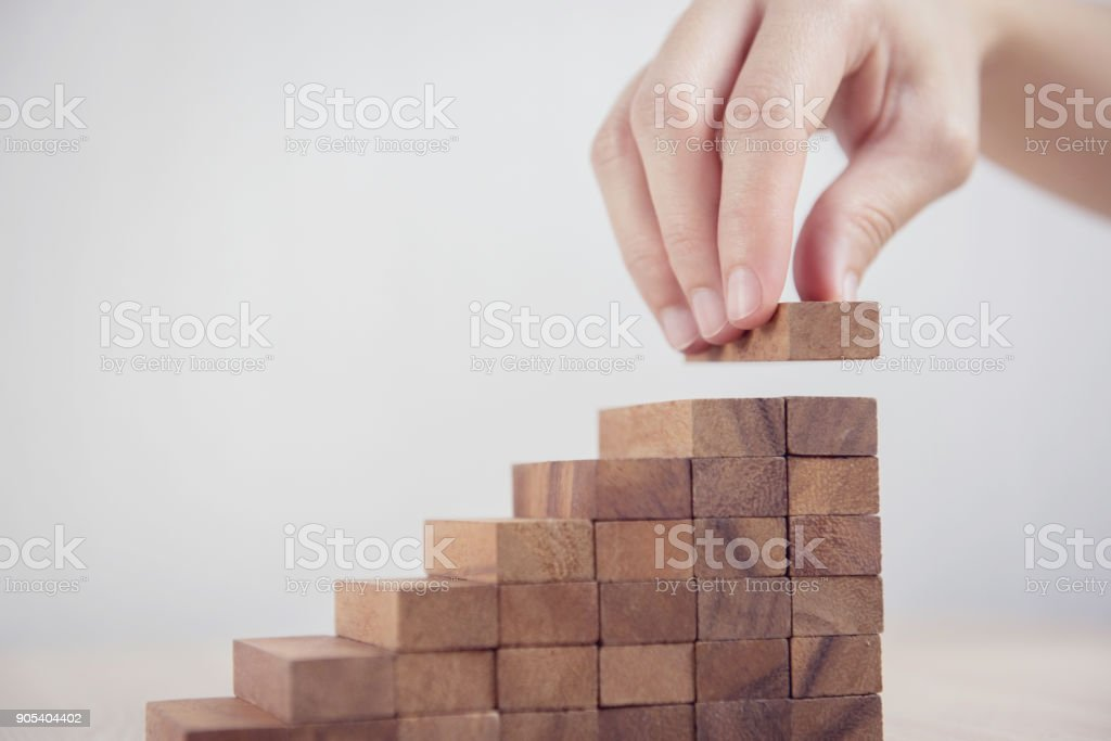 Woman hand arranging wood block stacking as step stair. Business concept growth success process. stock photo