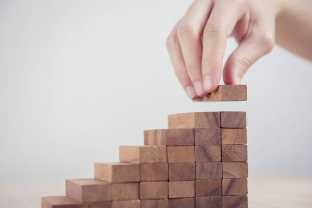Woman hand arranging wood block stacking as step stair. Business concept growth success process. Close up Woman hand arranging wood block stacking as step stair. Business concept growth success process. continuity stock pictures, royalty-free photos & images