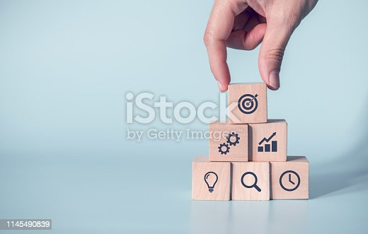 istock Woman hand arranging wood block with icon business strategy and Action plan, copy space. 1145490839