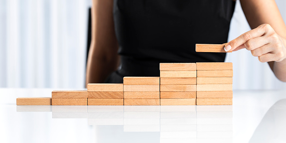 Female hand arranging wood block stacking as step stair. Ladder career path concept for business growth success process