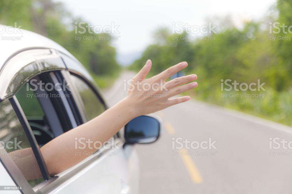 Woman hand at the car window stock photo