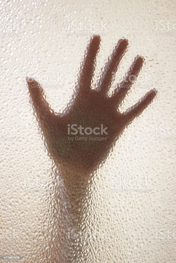 Woman hand behind a glassy window stock photo