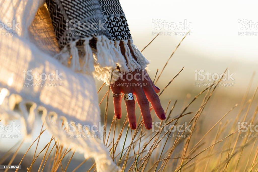 Woman hand caressing grass Woman hand caressing grass in nature near the sea at sunset 30-39 Years Stock Photo