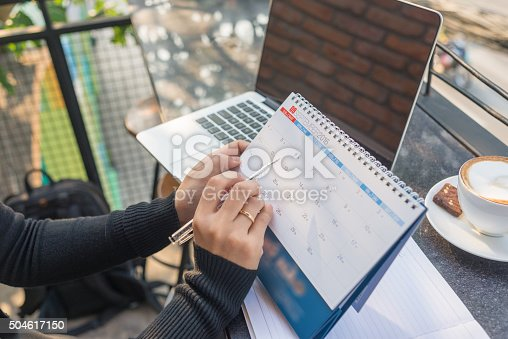 istock Woman hand carrying calendar and pointing on it by pen 504617150