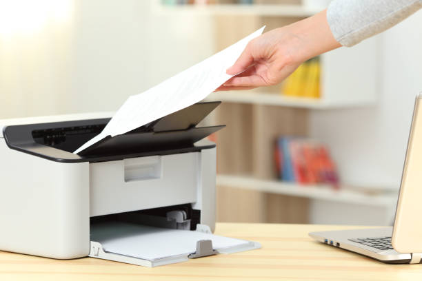 Woman hand catching a document from a printer stock photo