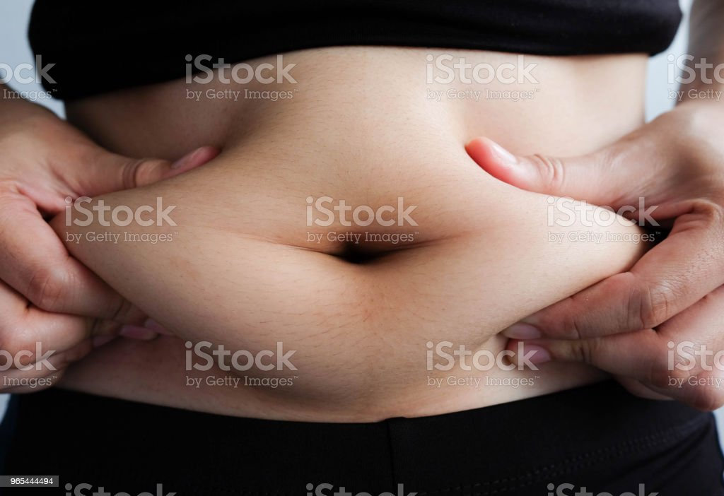 woman hand catching fat body belly paunch , diabetic risk factor royalty-free stock photo