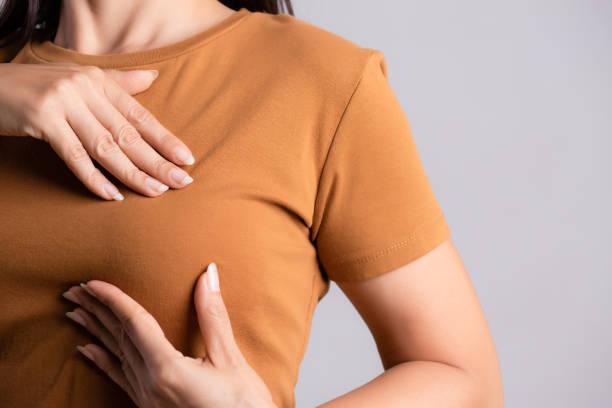 mão da mulher que verific protuberâncias em seu peito para sinais do cancro da mama no fundo cinzento. conceito dos cuidados médicos. - breast cancer - fotografias e filmes do acervo