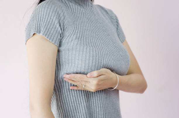 woman hand checking lumps on her breast for signs of breast cancer on crepe pink background, healthy lifestyle concept - seno foto e immagini stock