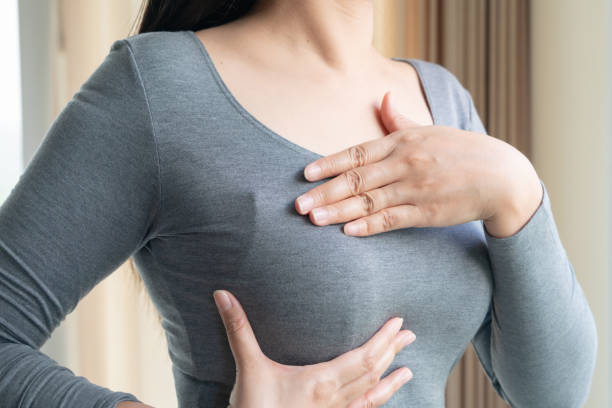 Woman hand checking lumps on her breast for signs of breast cancer. Women healthcare concept. stock photo
