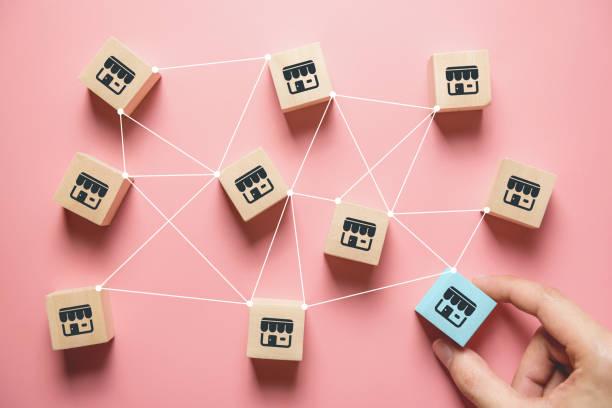 Frau Hand wählen Holz Blog mit Franchise-Marketing-System in globalen Netzwerk-Verbindung. Franchise-Geschäftskonzept. – Foto