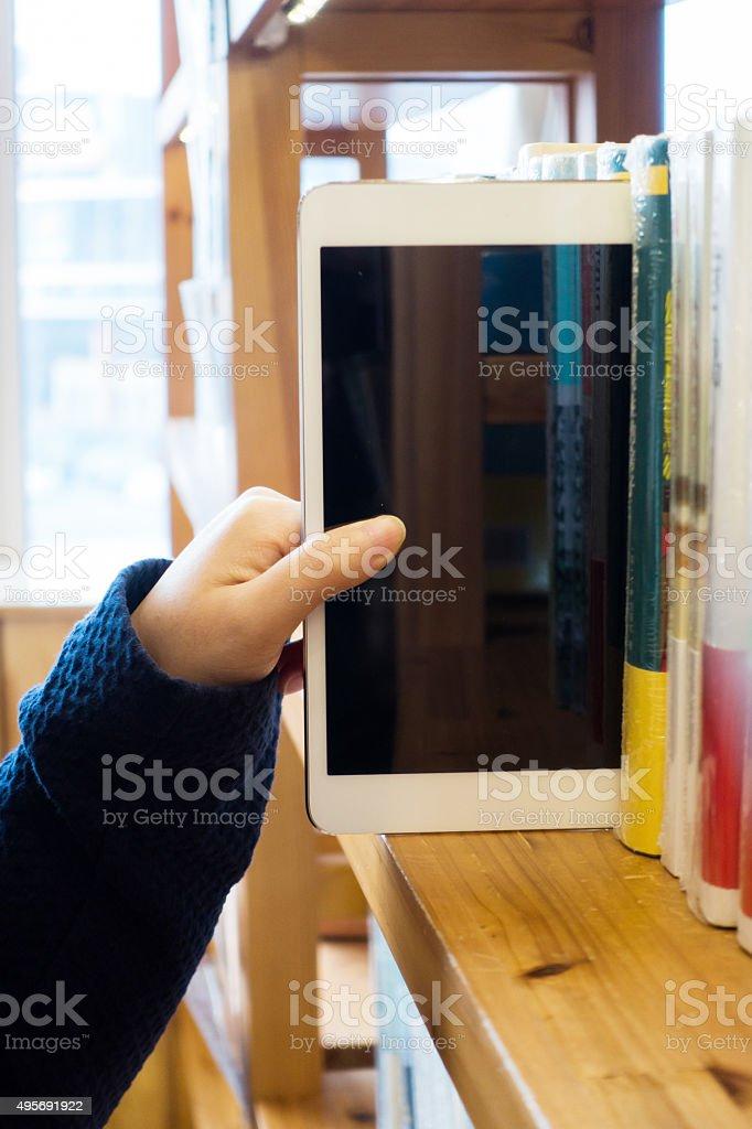 Mulher mão escolher tablet em uma estante - foto de acervo
