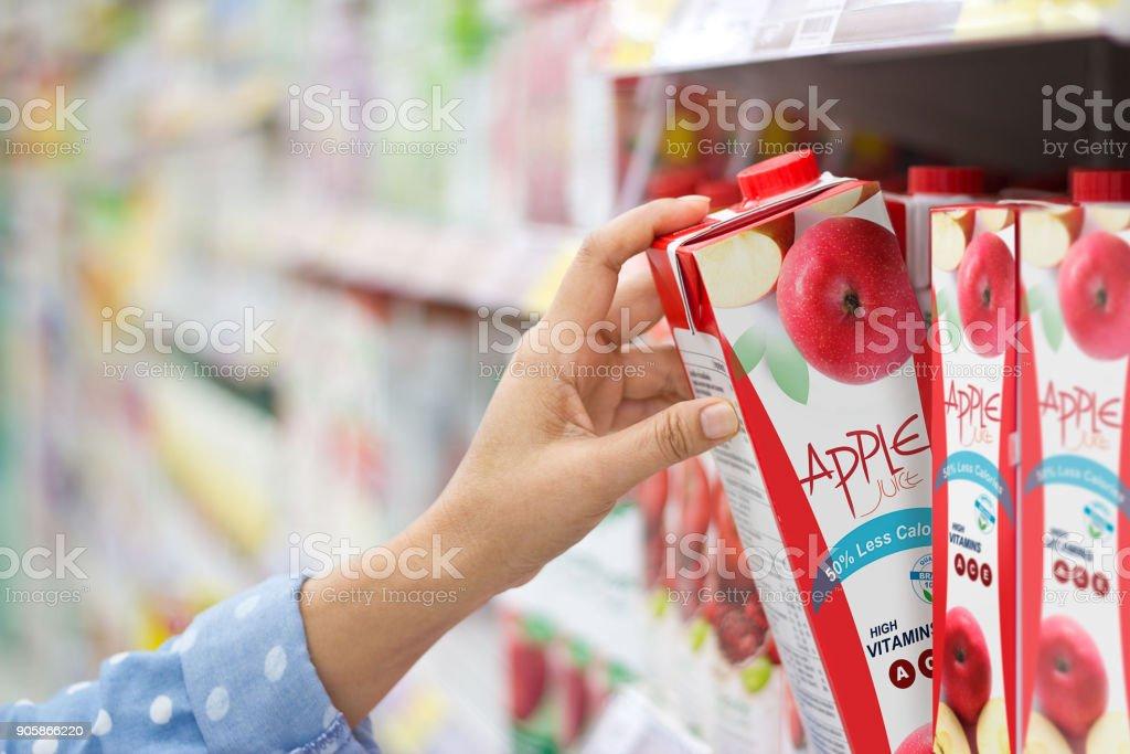 Woman hand choosing to buy apple juice on shelves in supermarket stock photo