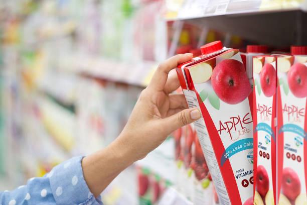 Mano de mujer elegir comprar zumo de manzana en los estantes de supermercado - foto de stock