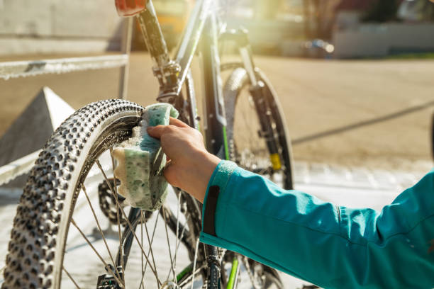 woman hand cleaning bicycle wheel with sponge. stock photo