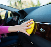 Woman hand cleaning car interior with cleaning sponge