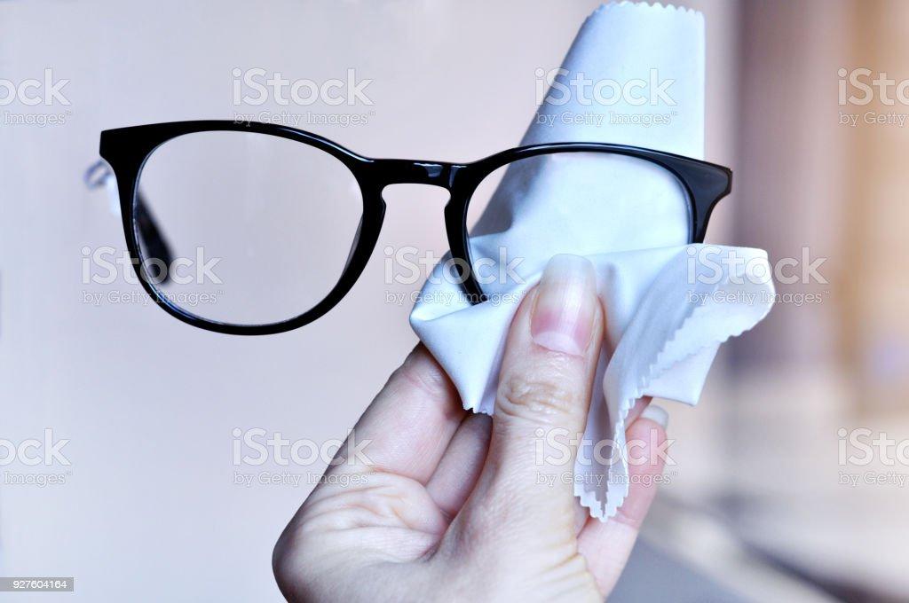 Die Hand der Frau trendige Schwarze Brillen Linse mit weißen Mikrofaser Tuch reinigen. Weichzeichnen Sie Hintergrund. Selektiven Fokus – Foto