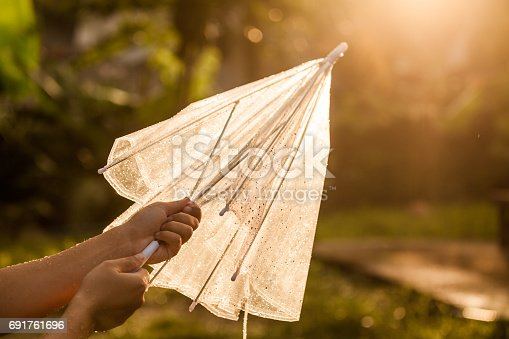 691761646istockphoto Woman hand close and keep an umbrella after rain 691761696