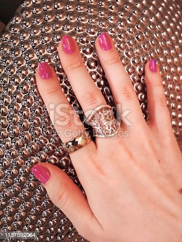 Woman hand coral pink manicure gel nail polish swatch beauty fashion silver decoration photo.