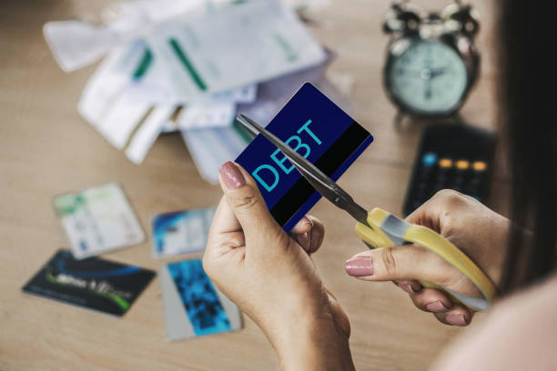 woman hand cutting credit cards by scissors with calculator and financial bills on desk woman hand cutting credit cards by scissors with calculator and financial bills on desk debt stock pictures, royalty-free photos & images