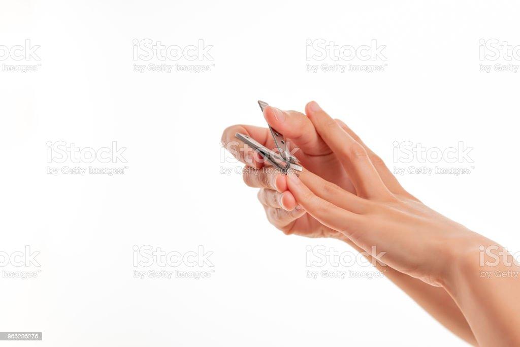 woman hand cutting nails using nail clipper on white backgrounds zbiór zdjęć royalty-free