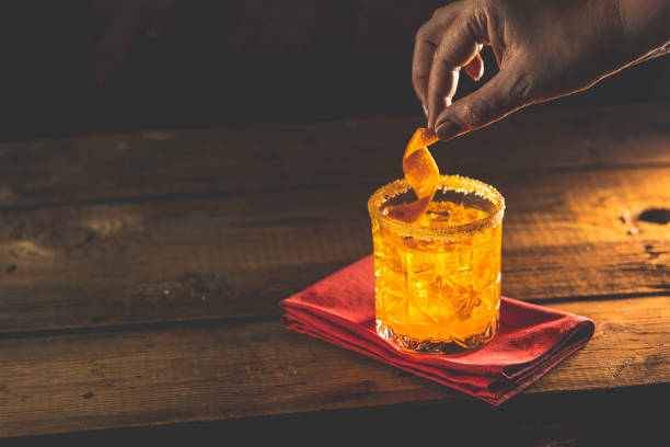 Woman hand decorate orange twist alcoholic cocktail negroni on old wooden board. Drink with gin, campari martini rosso and orange, an italian cocktail. Nice romantic backlight. stock photo