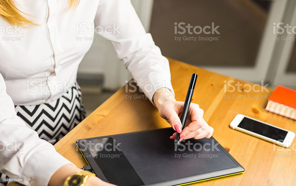 Woman hand drawing with graphics tablet, working designer stock photo