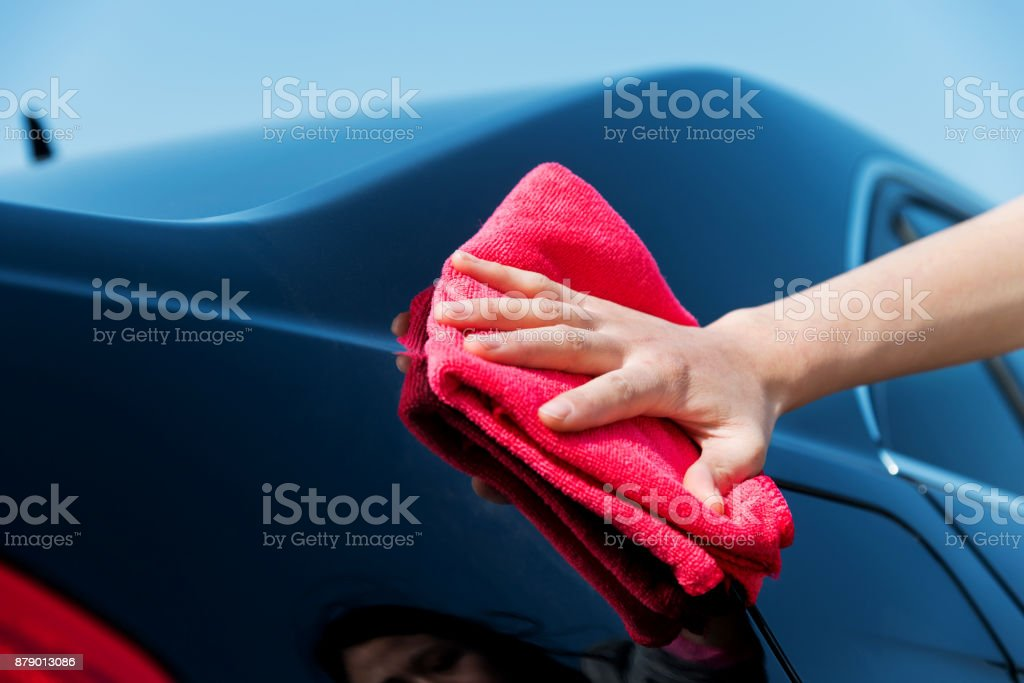 Woman hand drying the car with a red towel stock photo