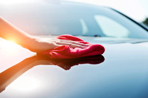 Woman hand drying the vehicle hood with a red towel stock photo