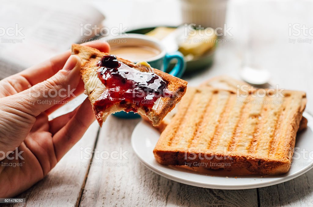 Woman hand eating toast for breakfast stock photo