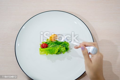 Top view of woman hands holding a fork while eating small portion salad over the table